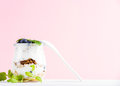 Yogurt oat granola with jam, blueberries and green leaves in glass jar on pink pastel backdrop Royalty Free Stock Photo