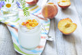 Yogurt with peaches slice selective focus slices on wooden table Stock Photos