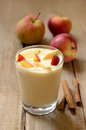 Yogurt with pieces of apple and peach in glass on wooden table Stock Photo
