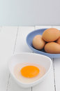 Yolk on white dish and wooden textured Royalty Free Stock Images