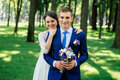 Yong beautiful smiling bride and groom hugs in the park. Bride embraces the groom. Couple in love at wedding day Royalty Free Stock Photo
