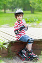 Yong sporting boy on rollers young with a bottle of water in city park Stock Photography
