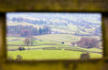 Yorkshire dales framed by gate white farmhouse and green fields in the an old wooden Stock Images