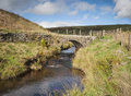 Yorkshire dales moorland packhorse bridge a small stream running smoothly under a stone in the Stock Image