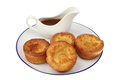 Yorkshires and gravy yorkshire puddings in a boat on a plate isolated against white Royalty Free Stock Photography