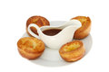 Yorkshires and gravy yorkshire puddings with in a jug on a plate isolated against white Royalty Free Stock Images