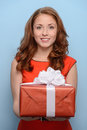 This is for you attractive young woman holding a gift box in he her hands standing against blue background Royalty Free Stock Photos