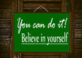 You can do it a motivational message on a green board with wooden background Royalty Free Stock Photos
