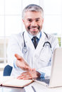 You can trust me confident mature grey hair doctor stretching out hand and smiling while sitting at his working place Stock Photos
