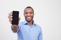It is for you cheerful black man stretching out a mobile phone and smiling while standing isolated on grey Royalty Free Stock Photography