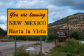 You are leaving new mexico hasta la vista sign metal road side that says your nm and another in the distance Royalty Free Stock Photography