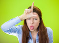 You are a loser closeup portrait angry mad upset pissed off young woman showing sign with hand on forehead isolated green Stock Photography