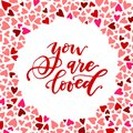 You are loved calligraphic phrase surrounded by colorful heart pattern