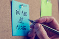 You are not alone man writing an inspirational message on a blue sticky note pinned to a cork board with a fountain pen Stock Photos