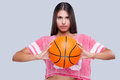 Are you ready to game confident young female cheerleader holding basketball ball and looking at camera while standing against grey Stock Photography