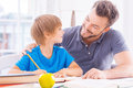 You are so smart cheerful young father helping his son with homework while sitting at the table together Stock Photos
