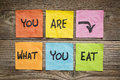 You are what to eat concept healthy lifestyle reminder words handwritten of colorful sticky notes against grained wood Stock Images