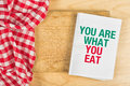 You are what you eat message in recipe notebook on kitchen table concept of guidelines for proper nutrition with copy space Stock Images