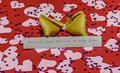 `You will find the love of your life` message in broken fortune cookie on red background covered with harts Royalty Free Stock Photo