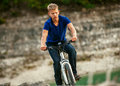 Youmg man riding a bike off road young extreme cyclist in mountain Royalty Free Stock Image