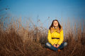 Youn girl sitting on yellow autumn grass brown Stock Photo