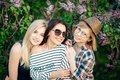 Three confident casual women standing at park and looking at camera Royalty Free Stock Photo