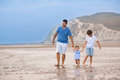 Young active father playing with his children on a beach baby daughter and son Royalty Free Stock Photo