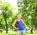 Young active female holding a soccer ball in a park shot with tilt and shift lens Royalty Free Stock Images