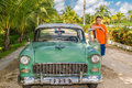 Young adolescent standing beside a vintage retro c handsome classic green car against tropical village background on summer warm Royalty Free Stock Image