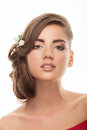 Young adorable brunette woman with low bun hairstyle, flower headpiece, and cute makeup posing with bare shoulders on white studio Royalty Free Stock Photo