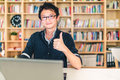 Young adult Asian man with laptop, thumbs up ok sign, home office or library scene, with copy space, success or technology concept Royalty Free Stock Photo