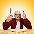 Young adult bold man sitting dinner table fork knife raised Stock Photos