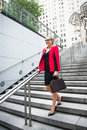 Young adult businesswoman walking on the steps from the office for the meeting and carrying bag Royalty Free Stock Photo