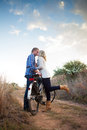 Young adult couple with old bicycle kissing yonug in dirt road Royalty Free Stock Photos