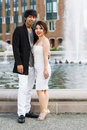 Young adult couple standing in front of water fountain vertical photo looking forward holding each other with geese and brick Royalty Free Stock Images