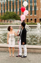 Young Adult Couple Watching Balloons as they hold them together Royalty Free Stock Photo
