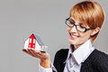 Young adult female holding a model house and looking to it isolated on grey Royalty Free Stock Image