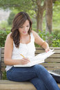 Young adult female student on bench outdoors attractive with books and pencil Stock Photo