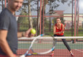 Young adult man playing tennis against woman Royalty Free Stock Photo