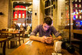 Young adult man texting in restaurant male teen sitting alone eating cake and Royalty Free Stock Photos