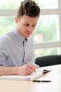 Young adult man writing note Royalty Free Stock Photo