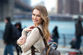 Young adult smiling student girl walking on city with many people around wearing sweater and carrying backpack Royalty Free Stock Photo