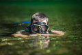 Young adult snorkeling in a river with goggles and scuba Stock Image