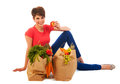 Young adult woman with heavy shopping bags pretty healthy vegetables and fruit is resting and eating an apple isolated over white Stock Photos