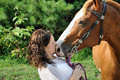 Young adult woman kissing her horse Stock Photography