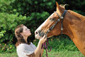 Young adult woman kissing her horse Royalty Free Stock Image