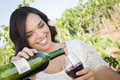 Young adult woman pouring a glass of wine in vineyard pretty mixed race enjoying the Stock Photography
