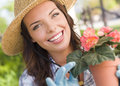 Young adult woman wearing hat gardening outdoors attractive happy Royalty Free Stock Photo
