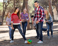 Young adults chasing ball outdoors at sunny day Stock Photo