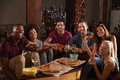 Young adults eating pizza at a party look to camera Royalty Free Stock Photo